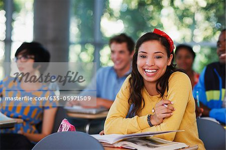 Student laughing at desk in classroom Stock Photo - Premium Royalty-Free, Image code: 635-05971509