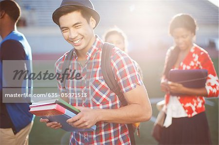 Student carrying books outdoors Stock Photo - Premium Royalty-Free, Image code: 635-05971513