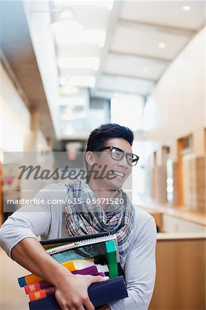 Student carrying stack of books in library Stock Photo - Premium Royalty-Free, Image code: 635-05971520