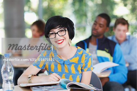 Student smiling at desk in classroom Stock Photo - Premium Royalty-Free, Image code: 635-05971521