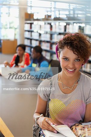 Student reading book in library Stock Photo - Premium Royalty-Free, Image code: 635-05971523