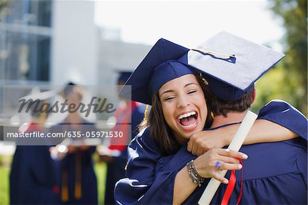 Smiling graduates hugging outdoors Stock Photo - Premium Royalty-Free, Image code: 635-05971530