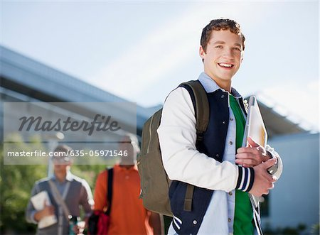 Student carrying folders outdoors Stock Photo - Premium Royalty-Free, Image code: 635-05971546