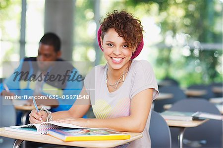 Student working at desk in classroom Stock Photo - Premium Royalty-Free, Image code: 635-05971548