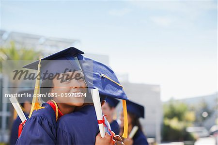 Smiling graduates hugging outdoors Stock Photo - Premium Royalty-Free, Image code: 635-05971574