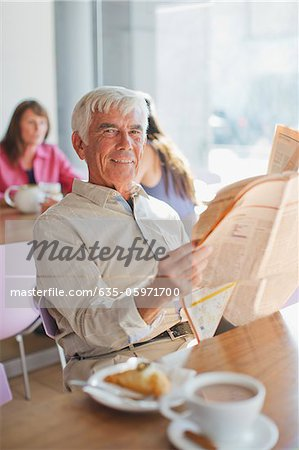 Man reading newspaper in cafe Stock Photo - Premium Royalty-Free, Image code: 635-05971700