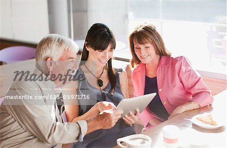 Family using laptop computer in cafe Stock Photo - Premium Royalty-Free, Image code: 635-05971716