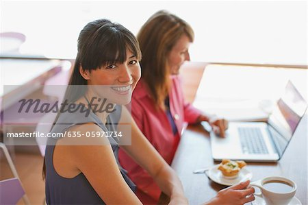 Businesswomen working together in cafe Stock Photo - Premium Royalty-Free, Image code: 635-05971734
