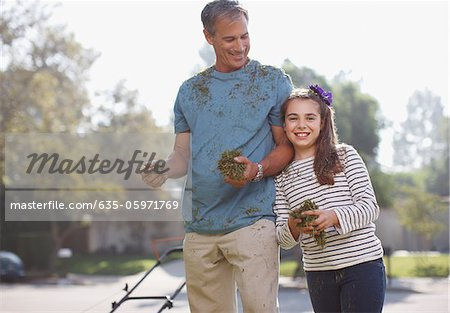 Father and daughter mowing lawn together Stock Photo - Premium Royalty-Free, Image code: 635-05971769