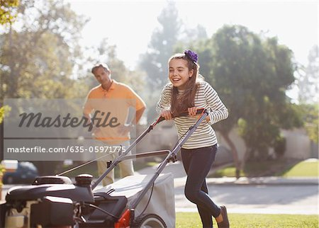 Father and daughter mowing lawn together Stock Photo - Premium Royalty-Free, Image code: 635-05971775
