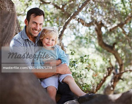 Father and son sitting in tree Stock Photo - Premium Royalty-Free, Image code: 635-05971778