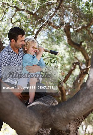 Father and son playing with telescope in tree Stock Photo - Premium Royalty-Free, Image code: 635-05971785