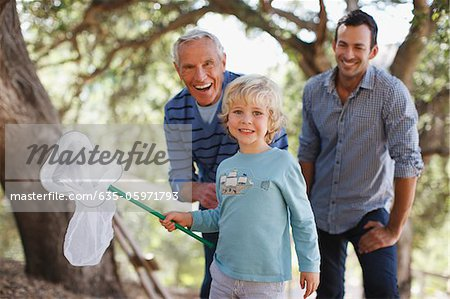 Three generations of men playing with butterfly net Stock Photo - Premium Royalty-Free, Image code: 635-05971793
