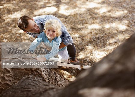 Father helping son climb tree outdoors Stock Photo - Premium Royalty-Free, Image code: 635-05971809