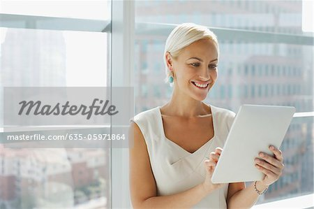Businesswoman using tablet computer in office Stock Photo - Premium Royalty-Free, Image code: 635-05971864