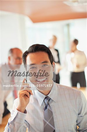Businessman talking on cell phone in office Stock Photo - Premium Royalty-Free, Image code: 635-05971937