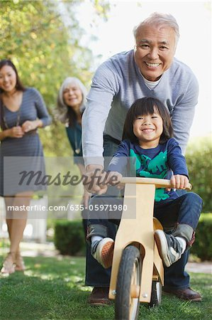 Older man pushing grandson in backyard Stock Photo - Premium Royalty-Free, Image code: 635-05971980