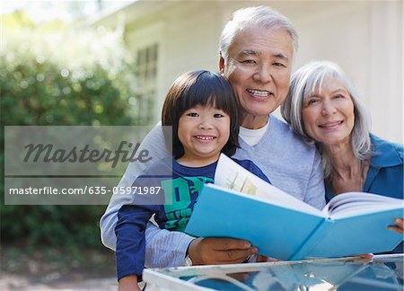 Older couple and grandson reading together Stock Photo - Premium Royalty-Free, Image code: 635-05971987