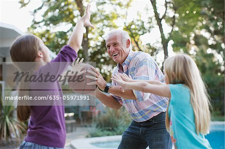 Older man playing basketball with granddaughters Stock Photo - Premium Royalty-Free, Image code: 635-05971991