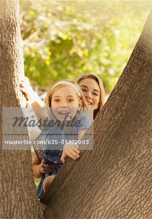 Mother helping daughter climb tree Stock Photo - Premium Royalty-Free, Image code: 635-05972003