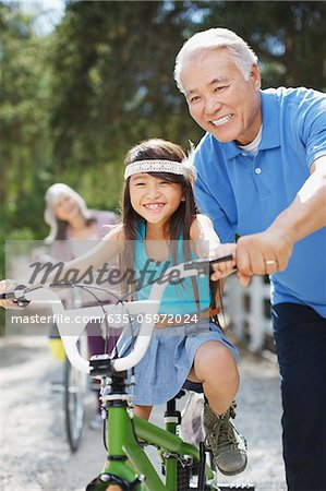 Older man helping granddaughter ride bicycle Stock Photo - Premium Royalty-Free, Image code: 635-05972024