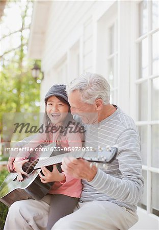 Older man and granddaughter playing guitar Stock Photo - Premium Royalty-Free, Image code: 635-05972038