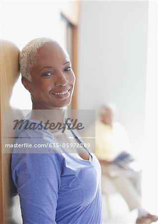Smiling older woman leaning against wall Stock Photo - Premium Royalty-Free, Image code: 635-05972089