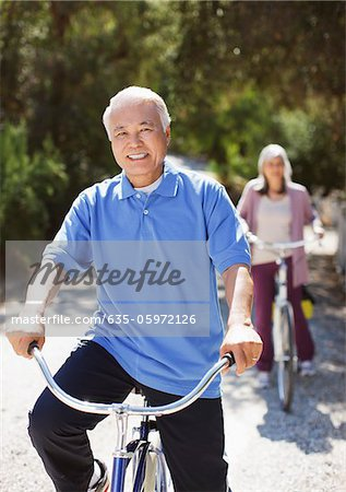 Smiling older couple riding bicycles Stock Photo - Premium Royalty-Free, Image code: 635-05972126