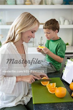 Mother slicing oranges for son Stock Photo - Premium Royalty-Free, Image code: 635-05972325