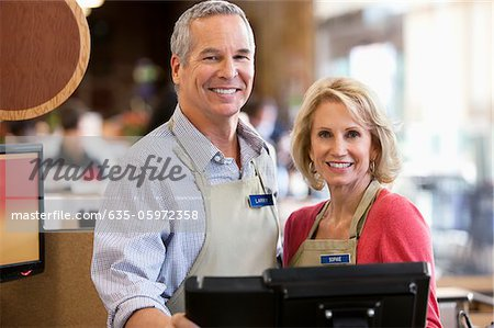 Workers using cash register in supermarket Stock Photo - Premium Royalty-Free, Image code: 635-05972358
