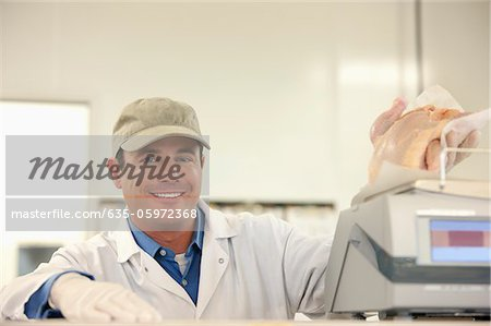 Butcher weighing meat behind counter Stock Photo - Premium Royalty-Free, Image code: 635-05972368