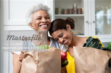 Mother and daughter unpacking groceries in kitchen Stock Photo - Premium Royalty-Free, Image code: 635-05972391