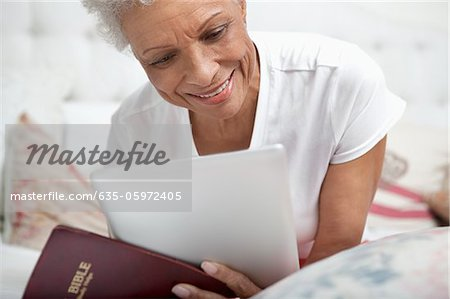 Older woman reading Bible and tablet computer Stock Photo - Premium Royalty-Free, Image code: 635-05972405