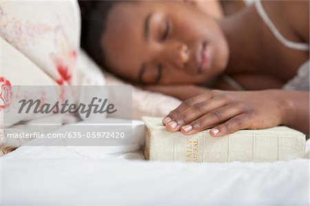 Girl asleep with Bible in bed Stock Photo - Premium Royalty-Free, Image code: 635-05972420