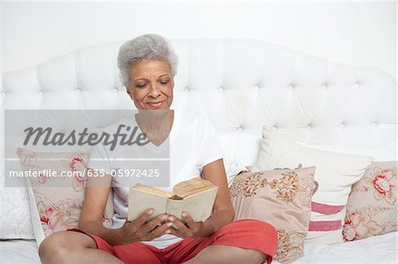 Older woman reading Bible on bed Stock Photo - Premium Royalty-Free, Image code: 635-05972425