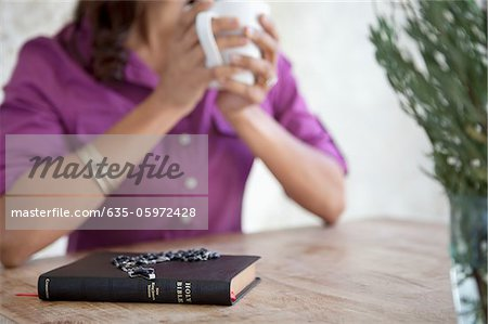 Prayer beads on Bible at breakfast table Stock Photo - Premium Royalty-Free, Image code: 635-05972428