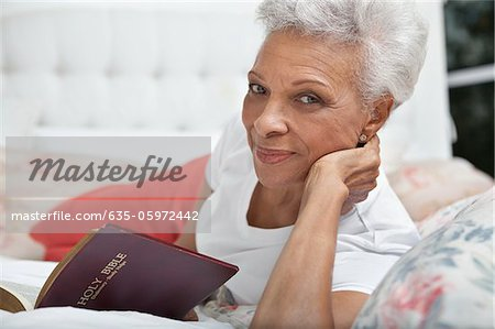 Older woman reading Bible in bed Stock Photo - Premium Royalty-Free, Image code: 635-05972442
