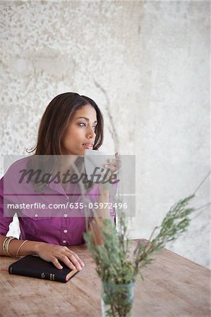 Woman having cup of coffee at table Stock Photo - Premium Royalty-Free, Image code: 635-05972496