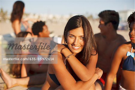 Woman sitting with friends on beach Stock Photo - Premium Royalty-Free, Image code: 635-05972614
