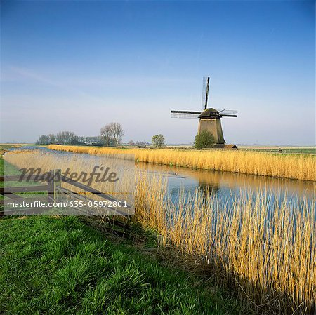 Windmill and wheatfield along rural river Stock Photo - Premium Royalty-Free, Image code: 635-05972801