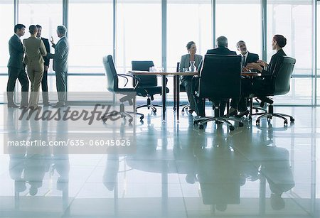 Business people meeting in separate groups in conference room Stock Photo - Premium Royalty-Free, Image code: 635-06045026