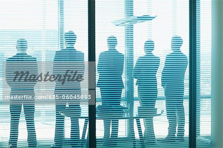 Silhouette of business people in a row looking out office window Stock Photo - Premium Royalty-Free, Image code: 635-06045053