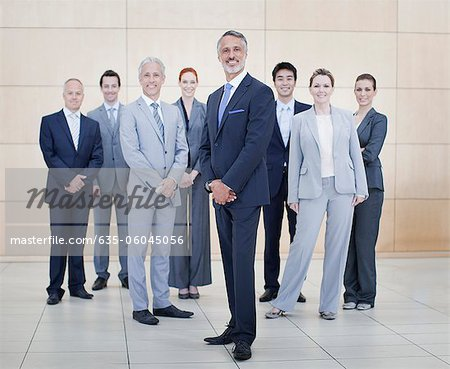 Portrait of smiling business people at bottom of escalator Stock Photo - Premium Royalty-Free, Image code: 635-06045056