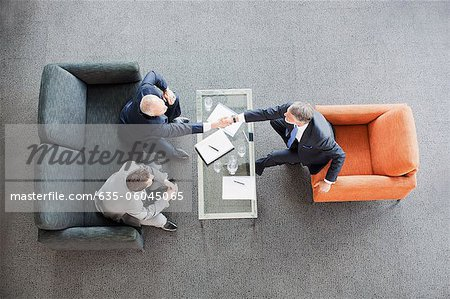 Businessmen shaking hands across coffee table in office lobby Stock Photo - Premium Royalty-Free, Image code: 635-06045065