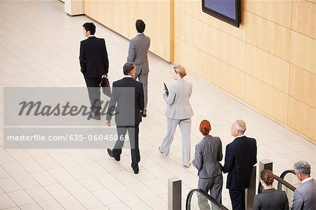 Business people stepping off escalator Stock Photo - Premium Royalty-Free, Image code: 635-06045069