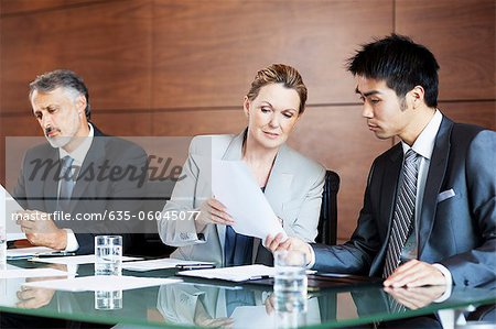 Businesswoman showing paperwork to businessman in meeting Stock Photo - Premium Royalty-Free, Image code: 635-06045077