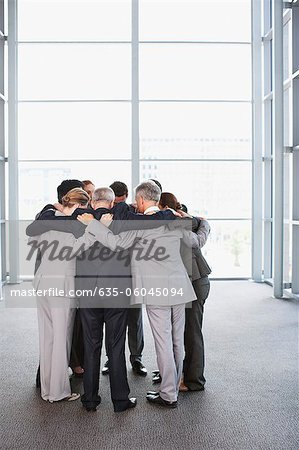 Business people standing in huddle Stock Photo - Premium Royalty-Free, Image code: 635-06045094
