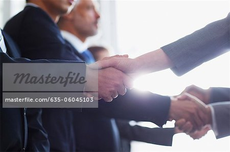 Close up of business people shaking hands in a row Stock Photo - Premium Royalty-Free, Image code: 635-06045103