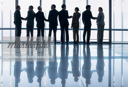 Business people shaking hands in a row at lobby window Stock Photo - Premium Royalty-Free, Image code: 635-06045104