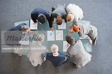 Business people huddled around paperwork on table Stock Photo - Premium Royalty-Free, Image code: 635-06045106